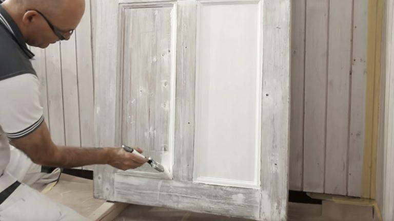 målar dörr med pensel