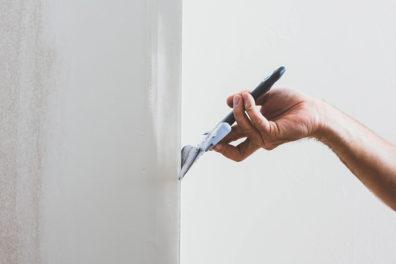 Spackel stryks på vägg med en bredspackel