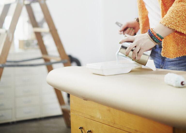Häll upp färg i rollertråg för måla byrå
